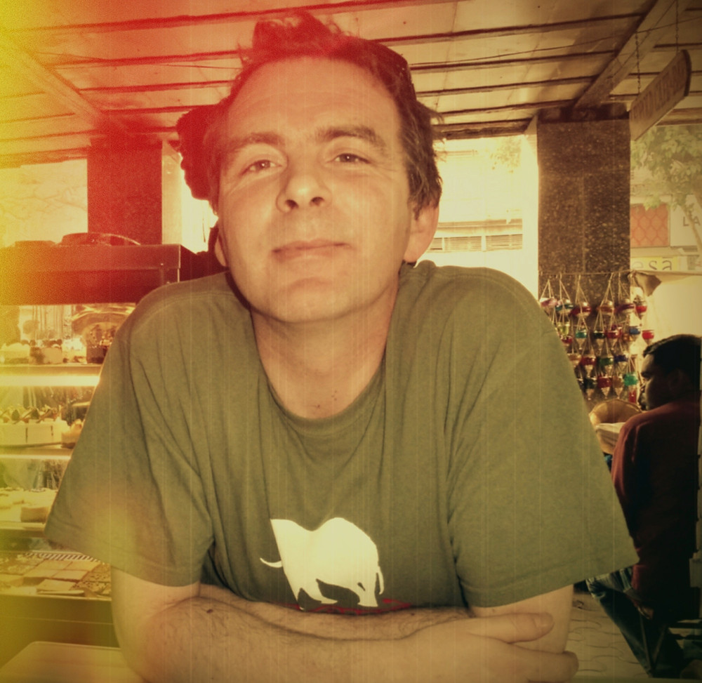 This is me looking happy in Leopolds Cafe, Mumbai, India in an green elephant T-Shirt