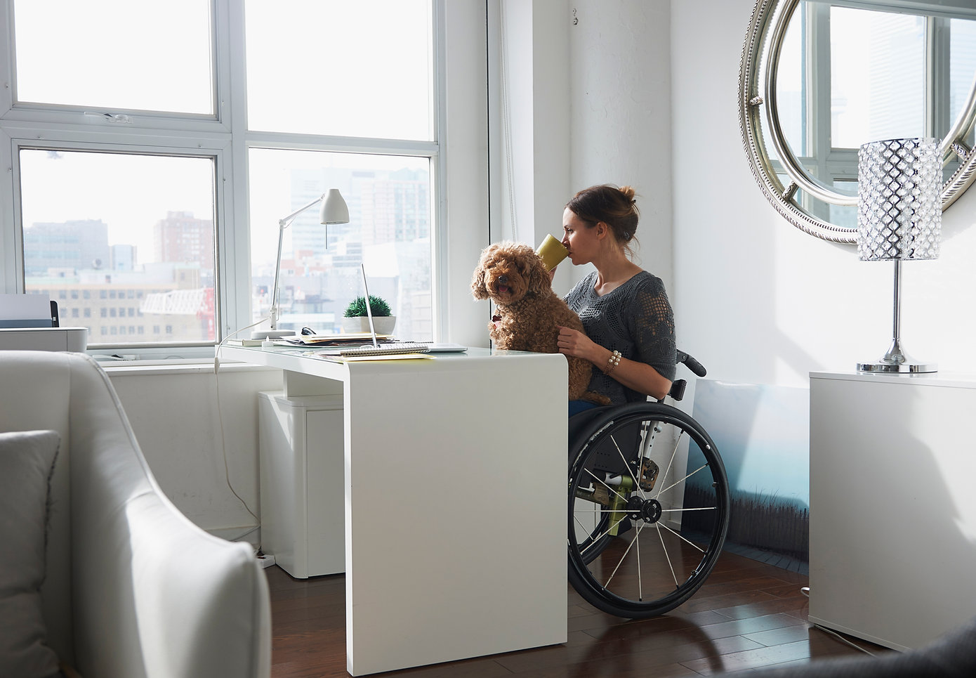 Woman in wheelchair drinking coffee while working at her desk with dog in her lap