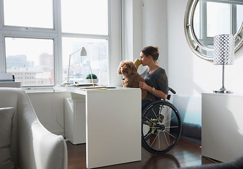 Woman in Wheelchair Drinking Coffee at her desk with a dog in her lap