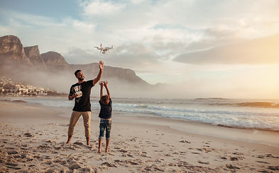 Father and son flying drone while on the beach.