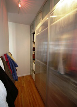Walk-in closet behind bed