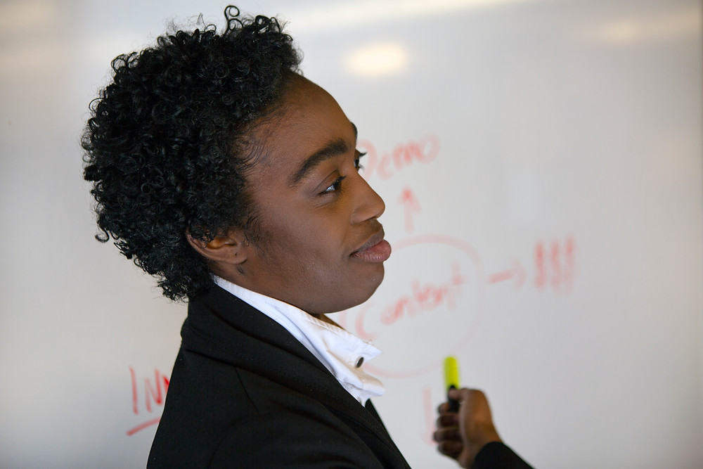 Black non-binary employee presenting at a meeting