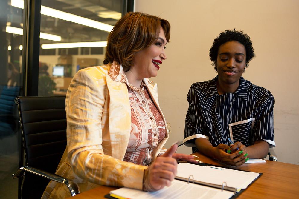 Transfeminine Latinx woman executive and Black non-binary employee in meeting