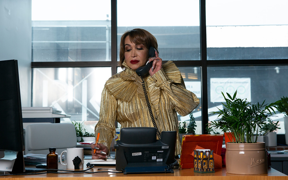 Transfeminine Latinx woman executive on the phone in her office.