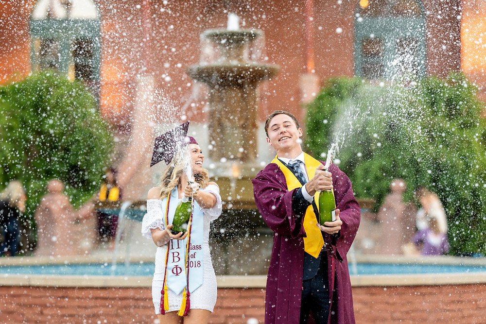 Graduation couple spraying champagne in front of old main