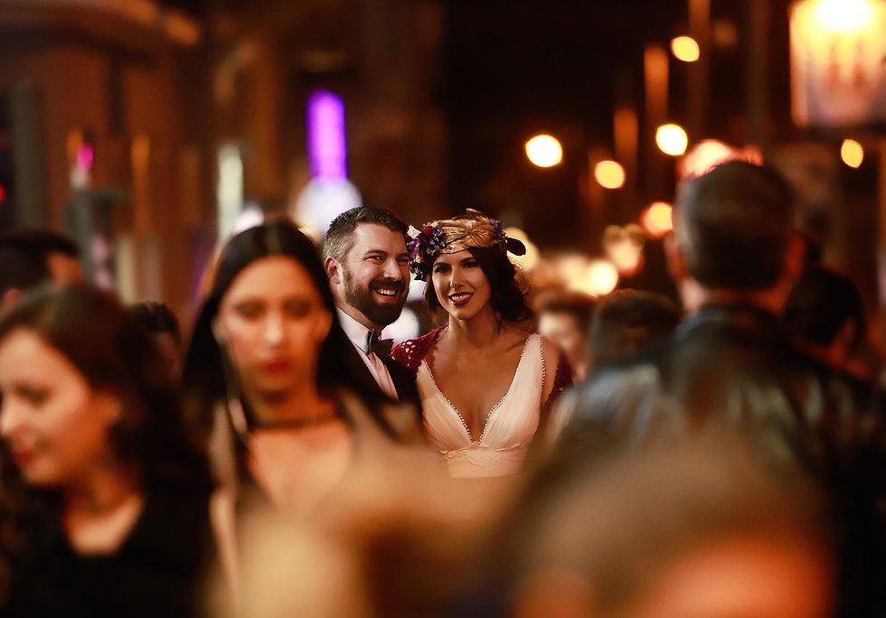 pareja de novios en gran via madrid sonrie entre la multitud mientras lorena riga les hace una foto como recuerdo de su boda