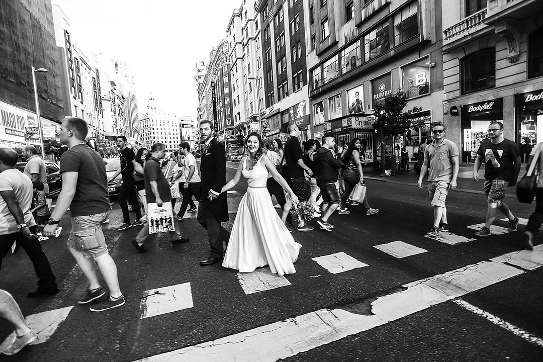 pareja de novios en paso de zebra gran via madrid caminan cogidos de la mano entre la multitud, la novia sonrie feliz mientras luce su vestido el novio impecable viste un frac