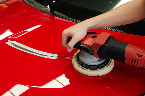 Hands with daul action polisher. polishing on car surface. hand and foam pad in blur motio