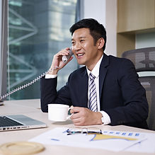 asian businessman talking on phone in of