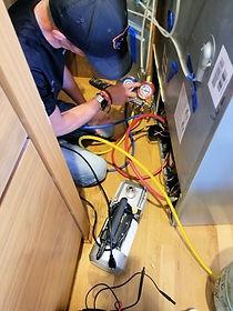 An appliace repair technian working on a refrigerator repair