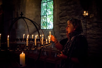 Photo of a Norwegian woman lighting candles in a church