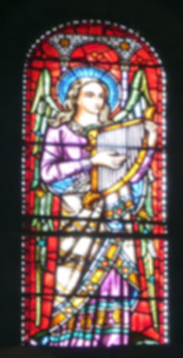 A detailed image of the the 'Angel of Music' stained glass window by Alexander Gibbs in the north transept of Romsey Abbey.