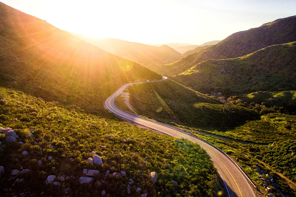 Photo of a road winding through valleys during sunset