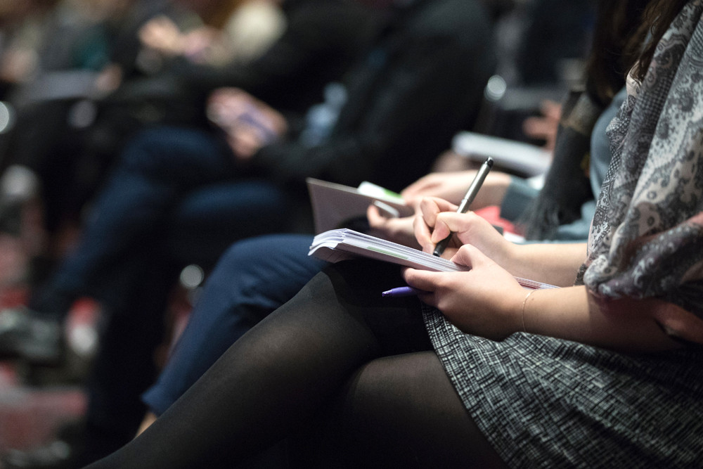 Woman taking notes at a conference
