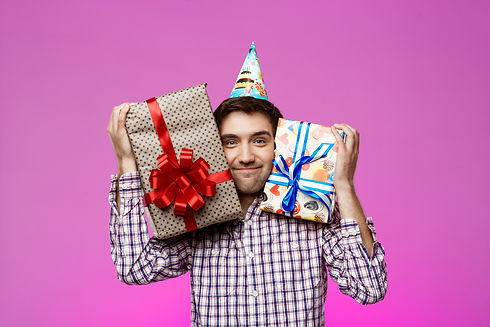 Happy man holding birthday gifts in boxe