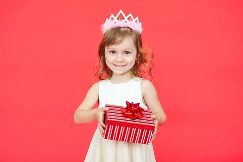 Little girl holding a gift box over red
