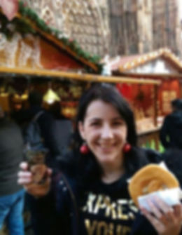 Strasbourg Christmas Market. Woman smiling a the camera holding hot spiced wine and a sweet bretzel.