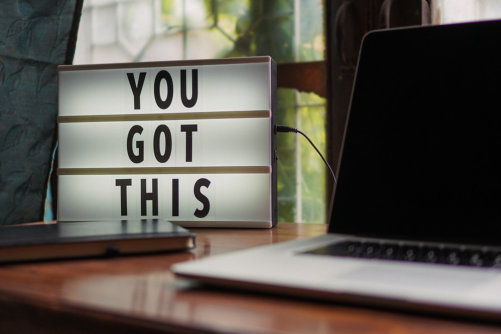 Decoration piece on a desk next to the laptop saying 'You got this'