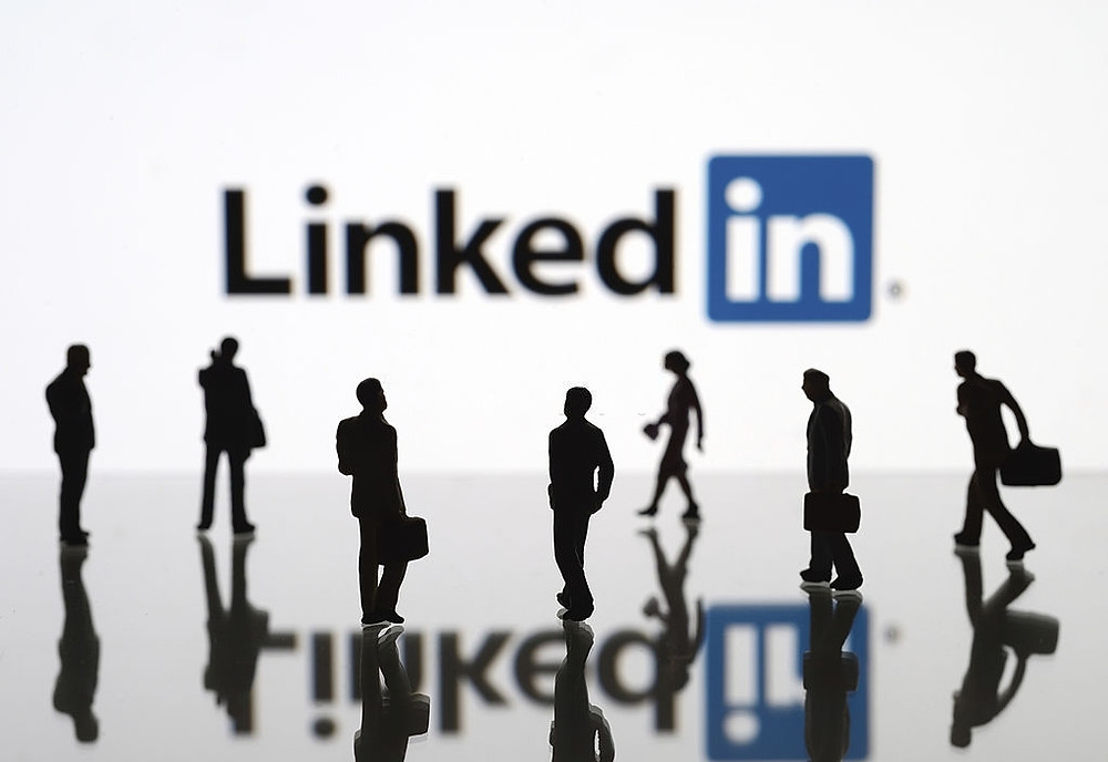 White background with Linkedin logo and workers walking in front