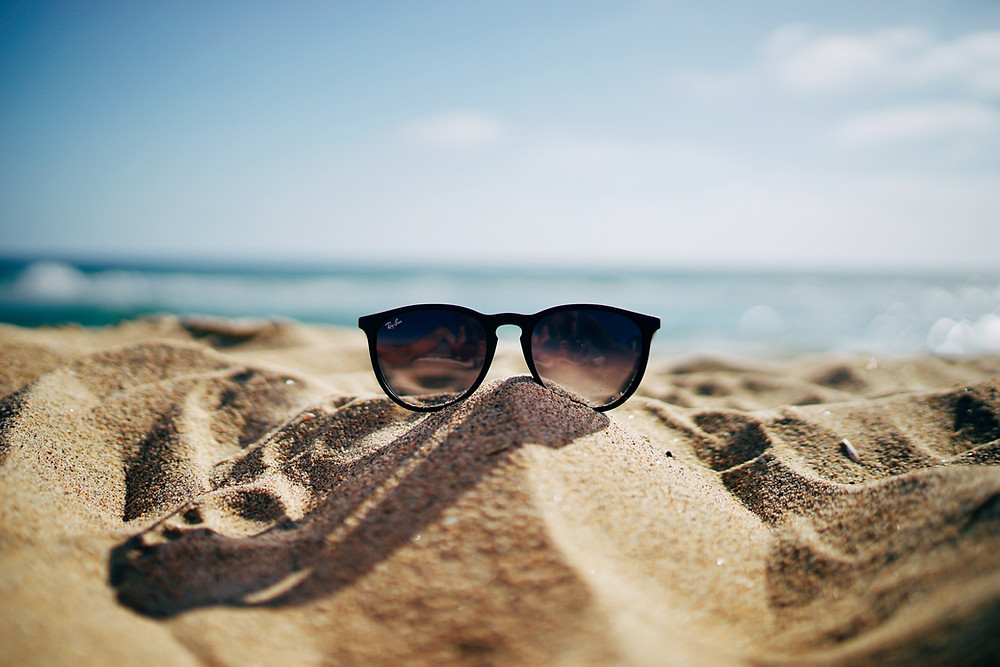 Photo of a beach with sunglasses on the sand