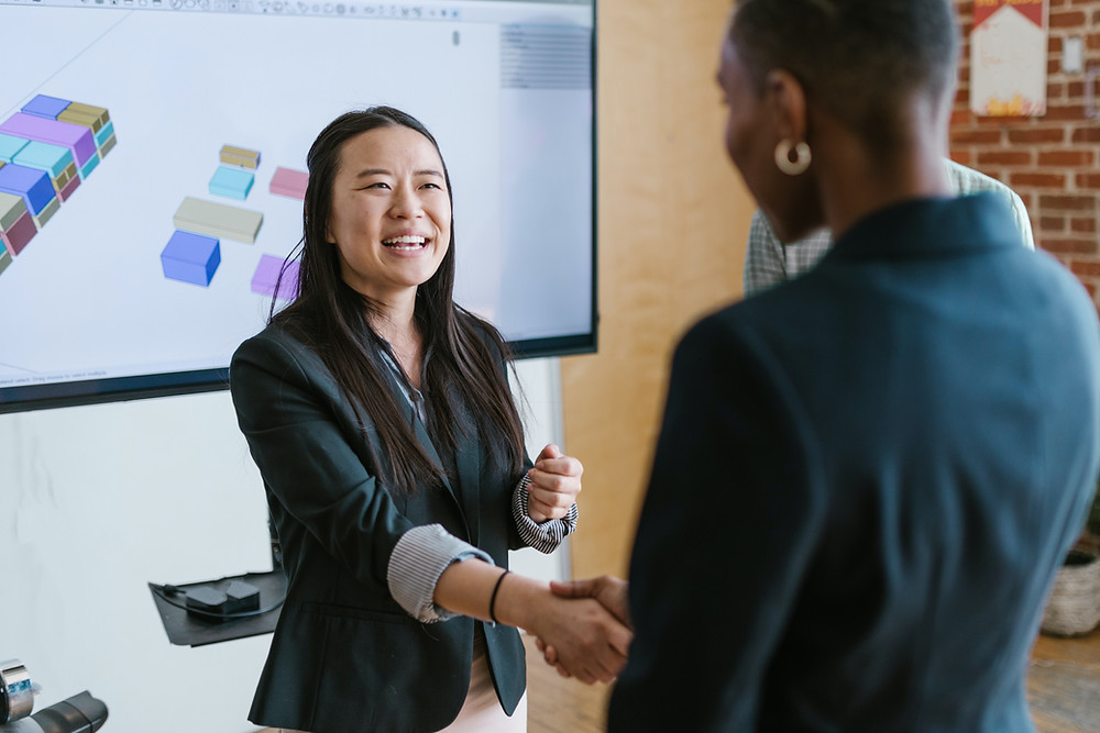 Two women shaking hands and smiling in work context.