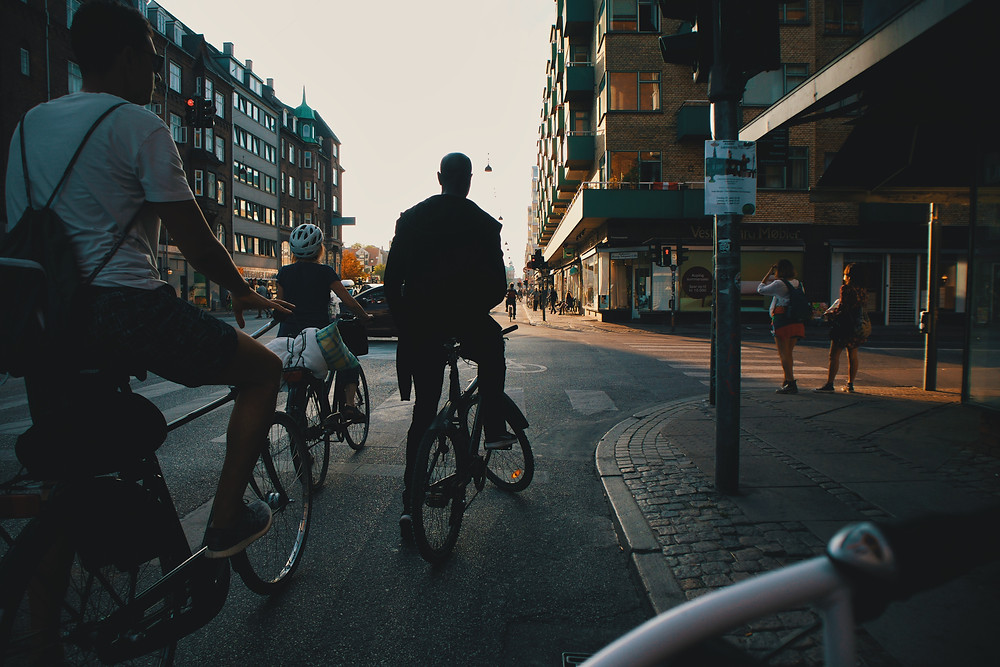 Group of people, adults and children, riding a bicycle on the streets of a city.