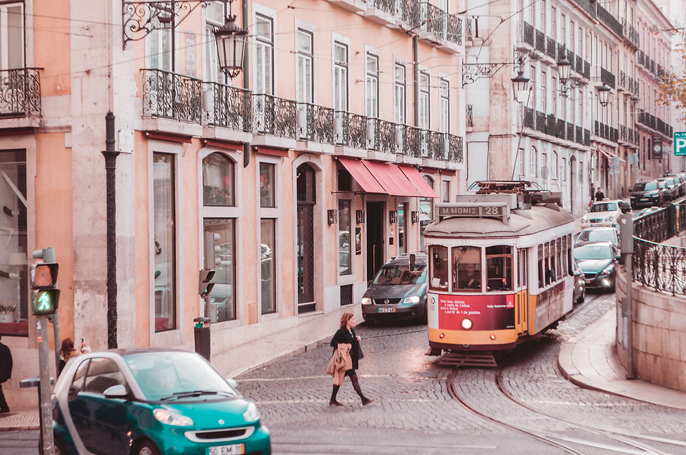 Tram, cars and a person crossing a Lisbon street.