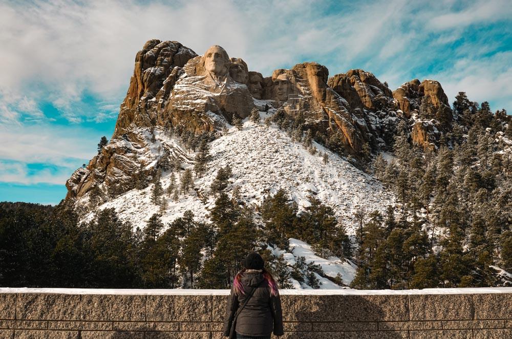 Jeune femme qui regarde vers des sculptures dans des montagnes en hiver. Mont Rushmore, Dakota du Sud
