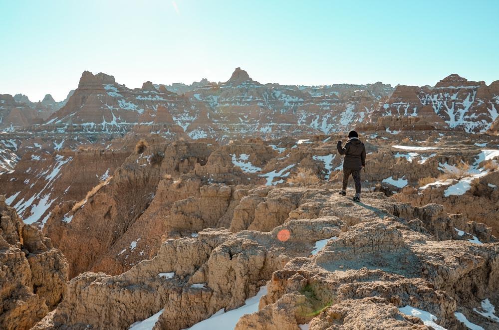 Jeune femme voyageuse se promenant dans les formations rocheuses enneigées dans un parc national. Badlands National Park, Dakota du Sud