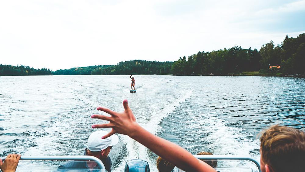 En tjej som åker på en wakeboard bräda efter en båt. Lycklig över att ha lyckats ställa sig upp och klarar av det!