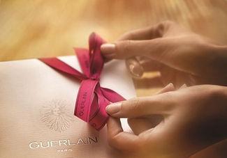 A woman holding a Guerlain gift certificate.
