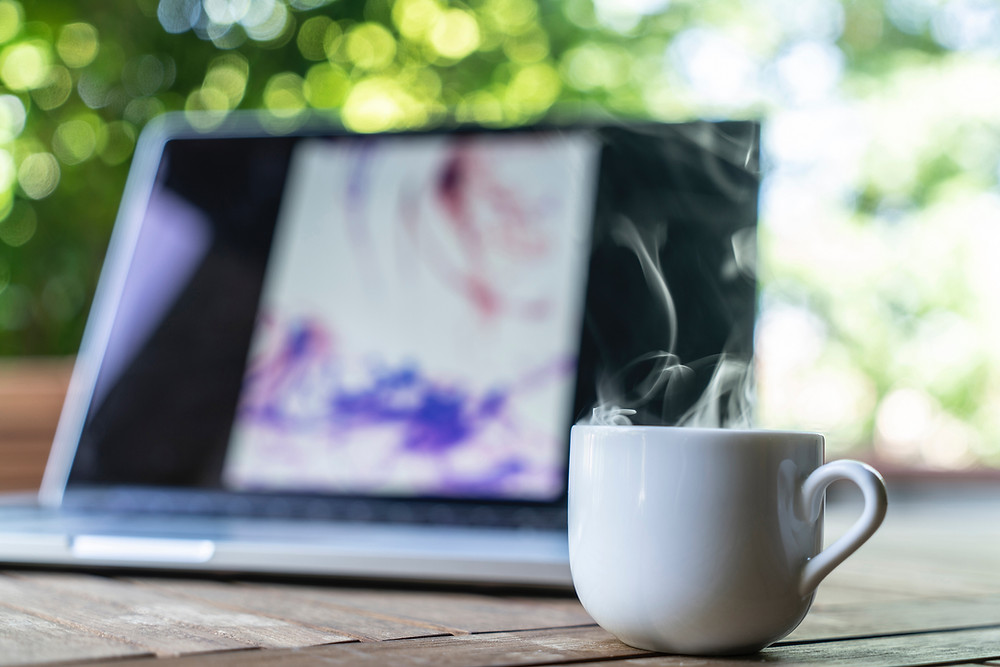 Laptop with coffee cup steaming beside