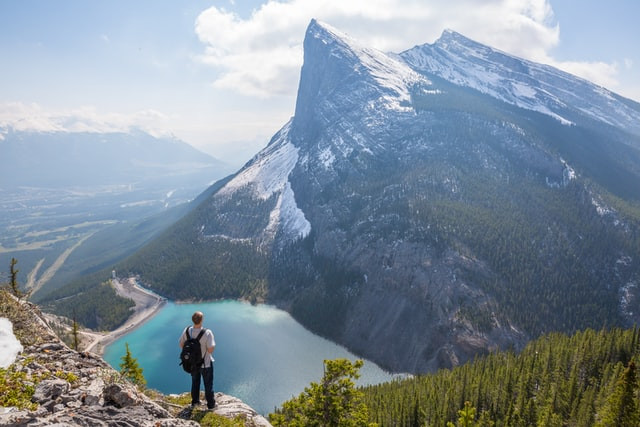 Person ontop of mountain overlooking lake