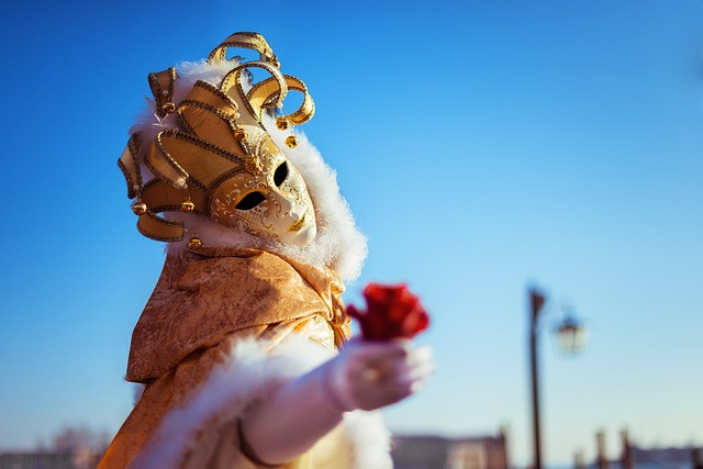Masquerade actor holding out a flower.
