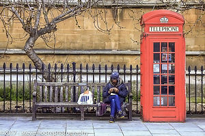 Man on a bench by a telephone box