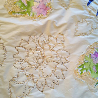 Stitched flowers on a cream surface on top...