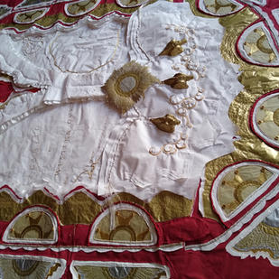 The red and white of the dress represent, amongst other things, blood and bandages.