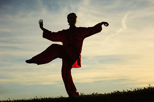 Woman praticing tai chi chuan at sunset.