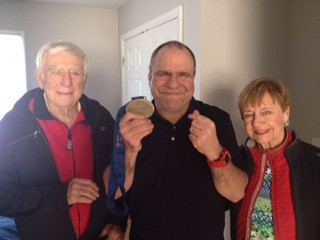 Michael sharing off one of his many special Olympic medals with his very proud parents (Ed & Marge).