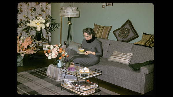 Woman in the 1960's posed on a couch with a cup of tea