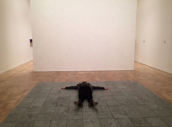 "The writer lying on Carl Andre's ""144 Pieces of Zinc"" (1967)"