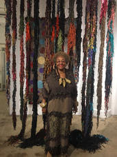 Installtion view, 2018. Rosemary Ollison in front of hanging leather sculpture, Portrait Society Gallery