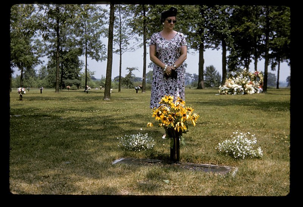 Woman at a cemetary with fresh flowers