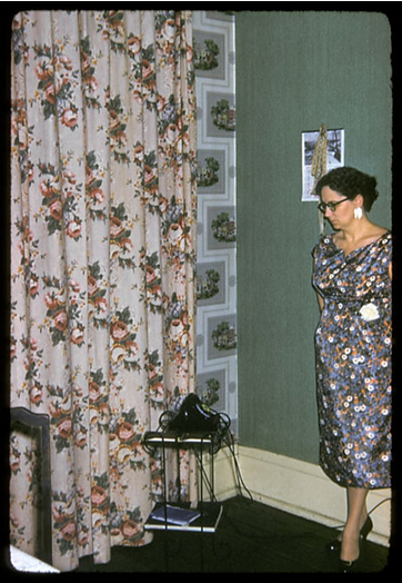 Woman in a 1960's setting near phone and curtain