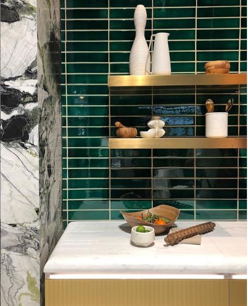 Green subway tile backsplash with marble in Kohler Kitchen with floating shelves