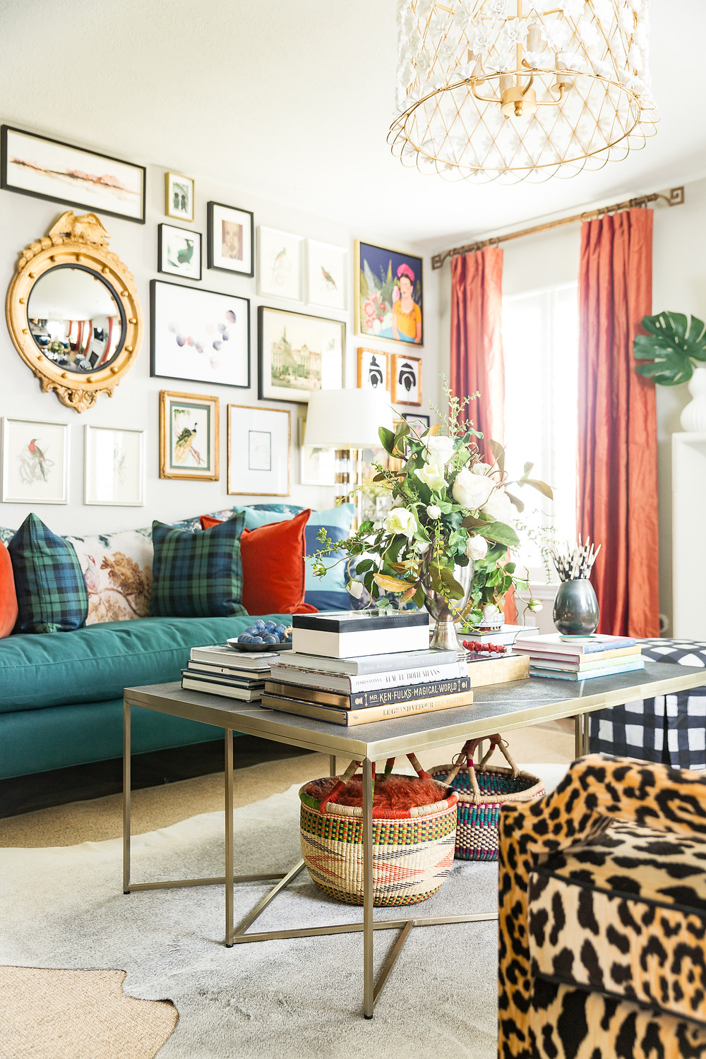 Maximalist living room with gallery wall, cheetah chairs, orange silk drapery and hide rug