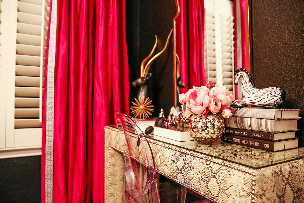 bedroom with fuchsia silk draperies and python upholstered vanity