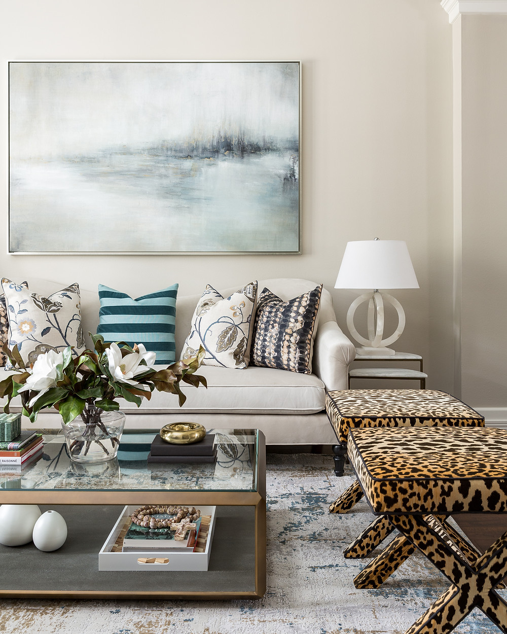 Formal Living Room With Large Scale Art, Cream Sofa, Elegant Custom Pillows, Alabaster Lamps, Glass Coffee Table, Cheetah Ottomans. Designed By Veronica Solomon. Photographed By Colleen Scott
