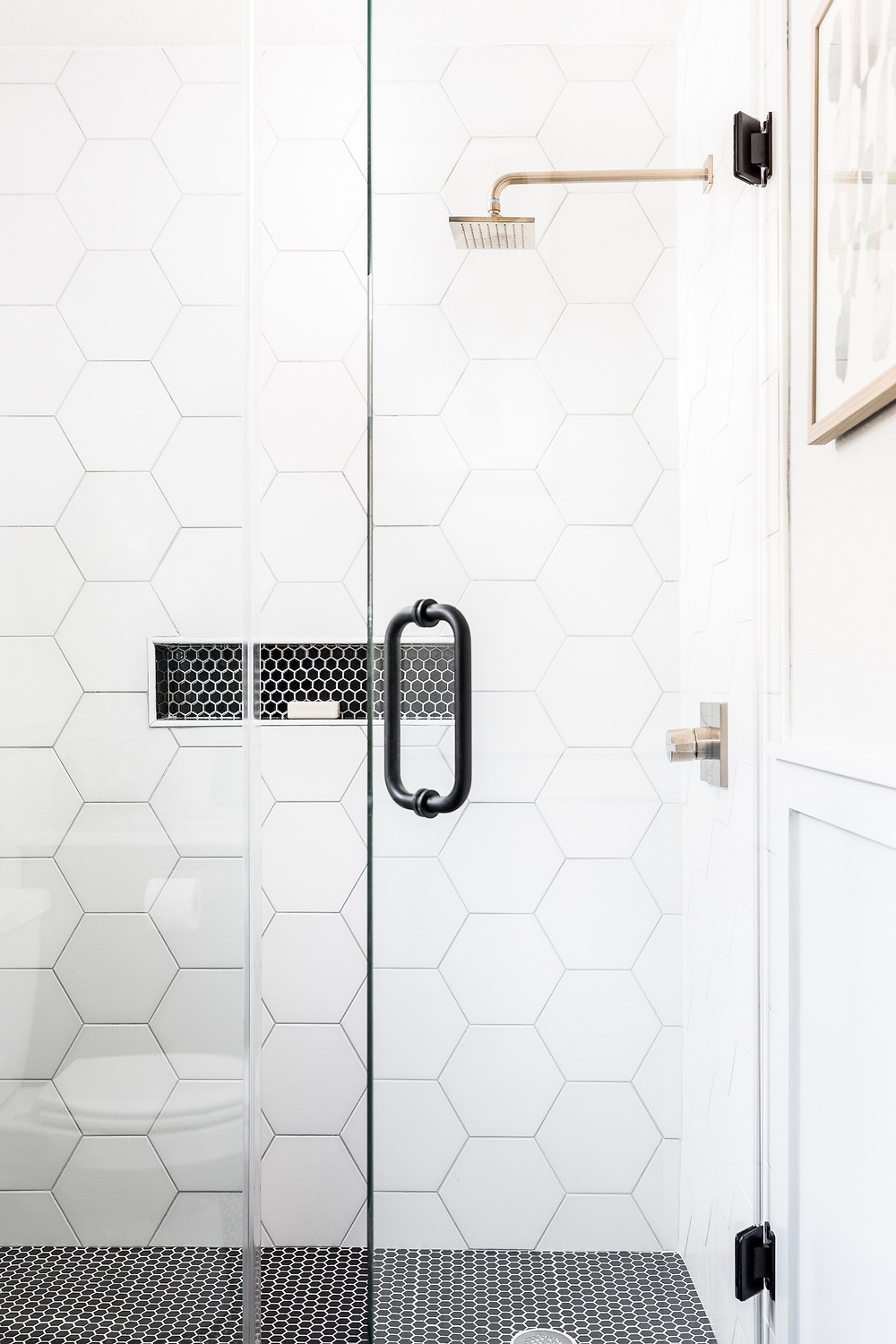 Shower with white hex tiles and black mosaic hex tiles on shower floor
