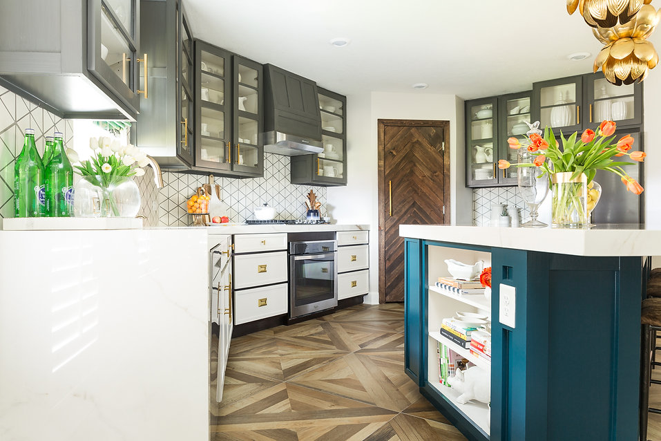 Kitchen with porcelain countertops, blue painted island and glass front cabinets